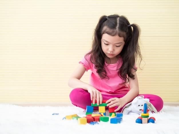 Pequeña muchacha linda asiática que juega bloques de madera en piso.