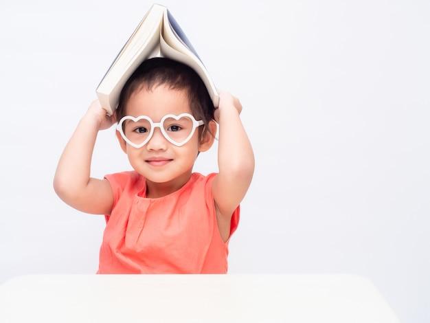 La pequeña muchacha linda asiática que lleva los vidrios y pone el libro en la cabeza