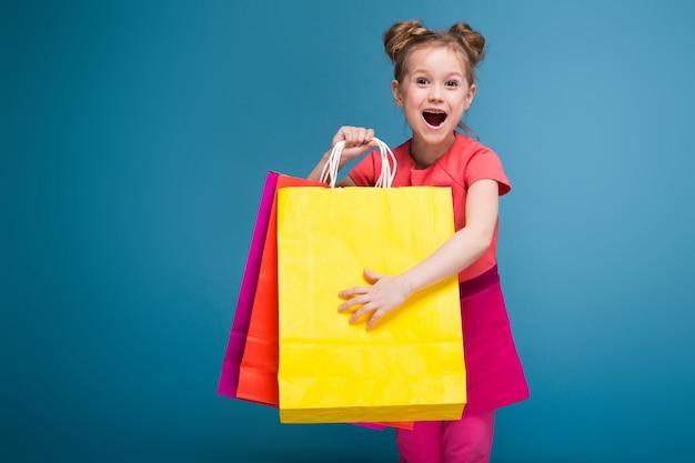 La pequeña muchacha linda atractiva en vestido rosado sostiene la bolsa de papel púrpura