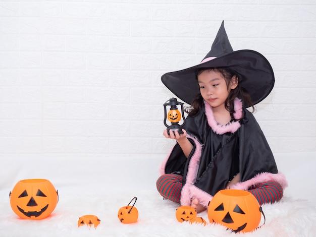 Pequeña muchacha linda cosplay como bruja y sosteniendo la lámpara y los cubos de las calabazas en el fondo blanco.
