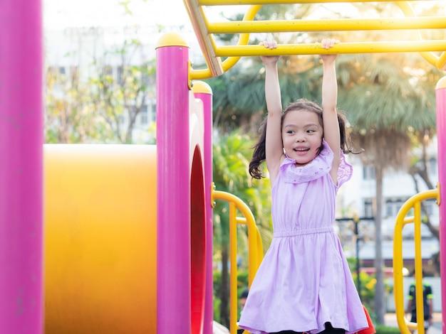 Pequeña muchacha linda feliz que cuelga la barra en el parque.