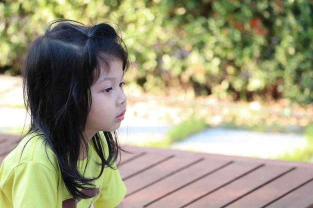 Pequeña muchacha linda que espera a alguien soledad en el patio en el jardín de la infancia.