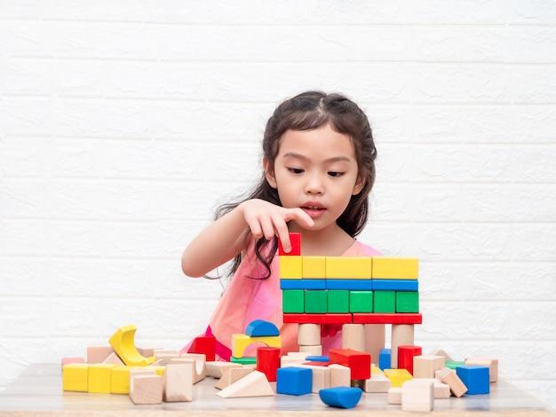 Pequeña muchacha linda que juega bloques de madera en la tabla y el fondo blanco de pared de ladrillos.