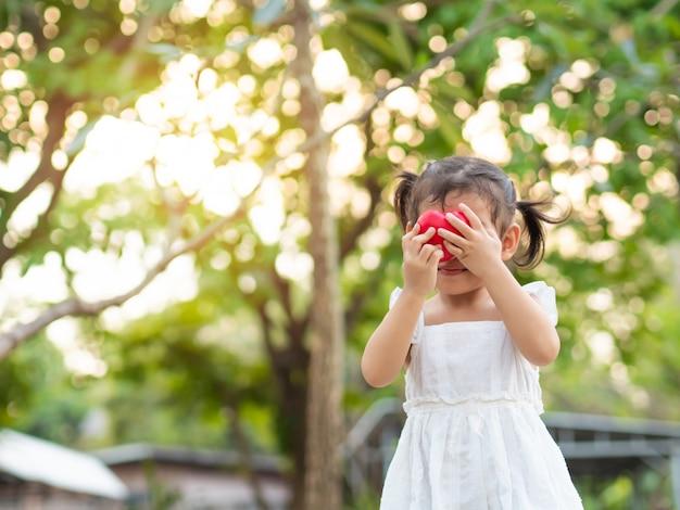 Pequeña muchacha linda que lleva a cabo un corazón rojo y cierre encima de su cara. un niño tímido mientras envía un corazón a su madre.