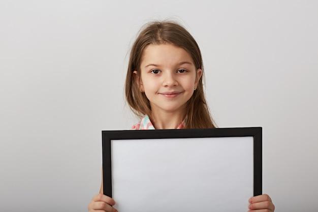 Pequeña muchacha del pelo oscuro que presenta con el marco vacío en estudio en el fondo blanco