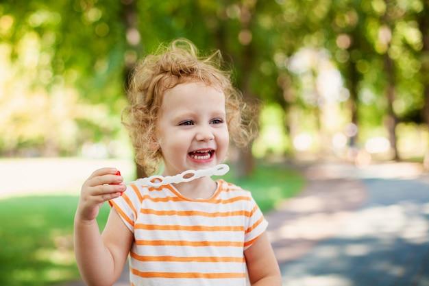 Pequeña muchacha rizada rubia que sopla burbujas de jabón en parque del verano