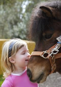 La pequeña muchacha rubia ama su retrato divertido del burro