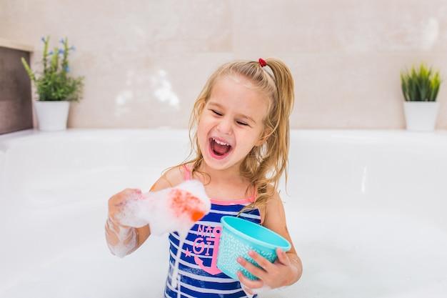 Pequeña muchacha rubia divertida que toma baño de burbujas en cuarto de baño hermoso. higiene de los niños. champú, tratamiento capilar y jabón para niños. copyspace