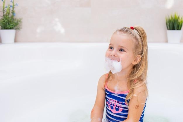 Pequeña muchacha rubia que toma el baño de burbujas en cuarto de baño hermoso. higiene de los niños. champú, tratamiento capilar y jabón para niños. niño bañándose en una bañera grande.