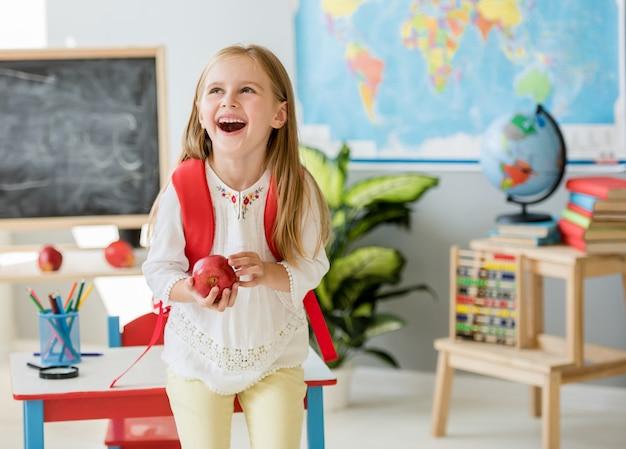 Pequeña muchacha rubia de risa que sostiene una manzana en el aula de la escuela