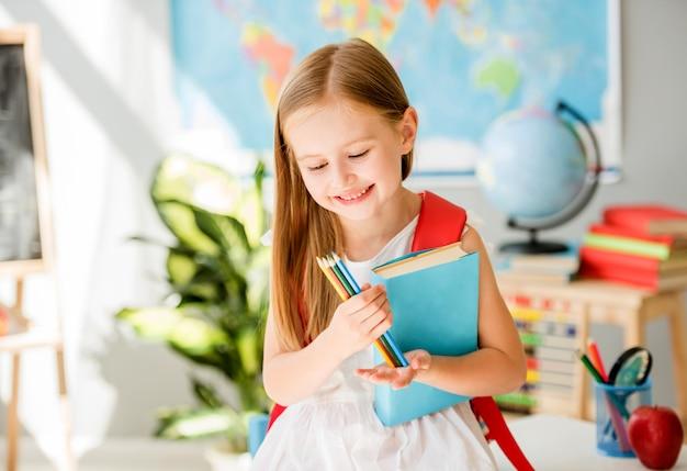 Pequeña muchacha rubia sonriente que sostiene el libro azul y que mira los lápices coloridos en la clase de escuela del sol