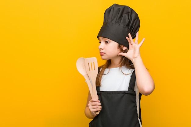 Pequeña mujer caucásica vistiendo un traje de chef tratando de escuchar un chisme.