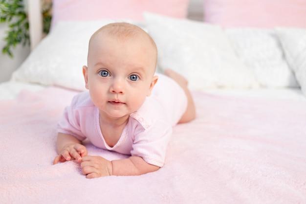 Pequeña niña de 6 meses gateando en una cama blanca y rosa en casa
