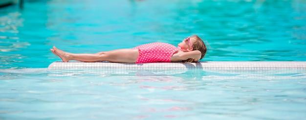 Pequeña niña adorable feliz en el borde de la piscina infinita al aire libre