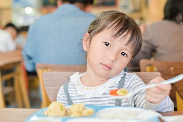 Pequeña niña asiática con cara infeliz mientras almuerza en la mesa en el restaurante, quisquilloso no quiere comer o no tiene hambre