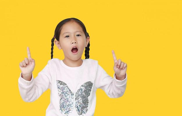 Pequeña niña asiática emocionada que señala dos índices para arriba aislados