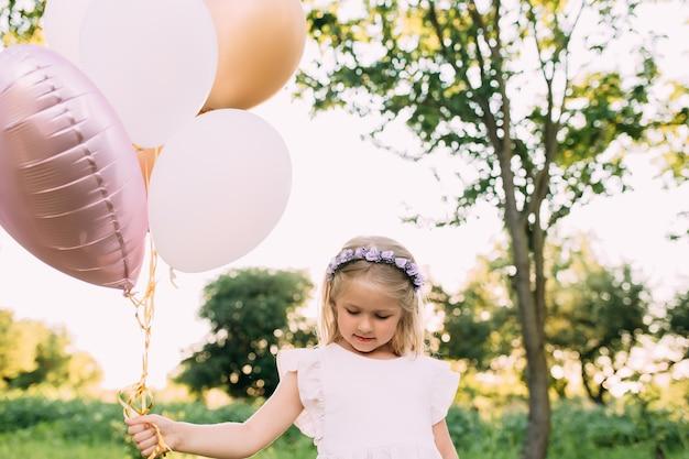 Pequeña niña brillante con globos rosas en el jardín.