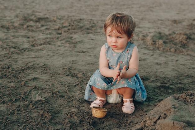 La pequeña niña caucásica se divierte cavando en la arena en la playa del océano, construyendo un castillo de arena
