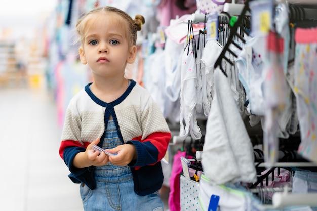 Una pequeña niña caucásica está de pie cerca de un escaparate con ropa y ropa interior en una gran tienda.