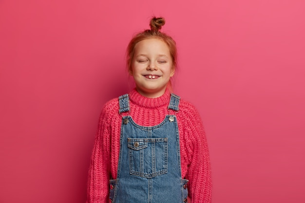 Pequeña niña de cinco años con moño de jengibre y dos dientes que sobresalen, viste un suéter de punto cálido y un sarafan de mezclilla, se ríe de alegría, mantiene los ojos cerrados, mira dibujos animados divertidos, aislados en la pared rosa