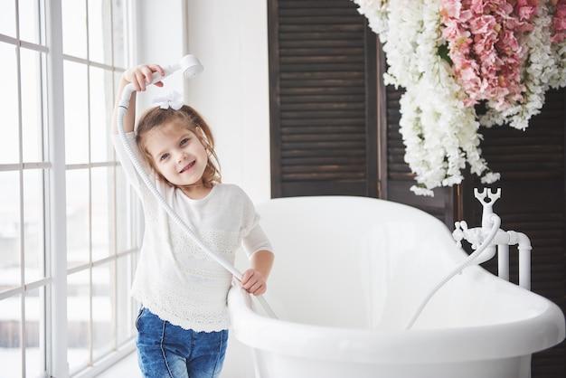 Pequeña niña divertida con el pelo rizado. prepárate para tomar un baño. amplio baño iluminado. un cuerpo sano y limpio. cuidar de ti mismo desde la infancia