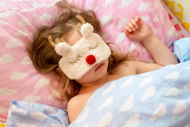 La pequeña niña duerme tranquilamente en la cama con una divertida máscara de felpa en forma de ciervo.