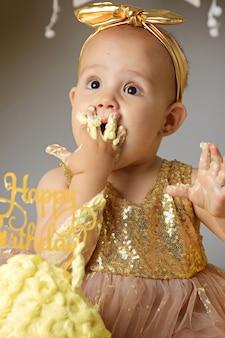Pequeña niña dulce en un vestido dorado con un lazo en la cabeza tratando de un pastel de gelatina de jazz de una crema. foto de estudio de un cumpleaños en una pared gris rodeada de bolas