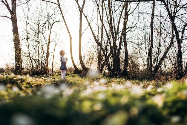 La pequeña niña se encuentra cerca de los árboles