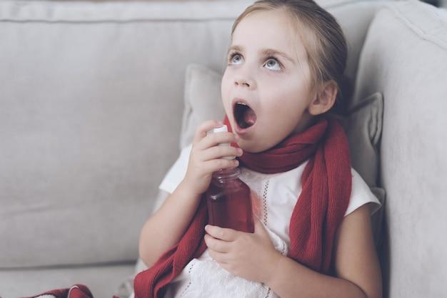 La pequeña niña enferma salpica el aerosol rojo en una garganta.
