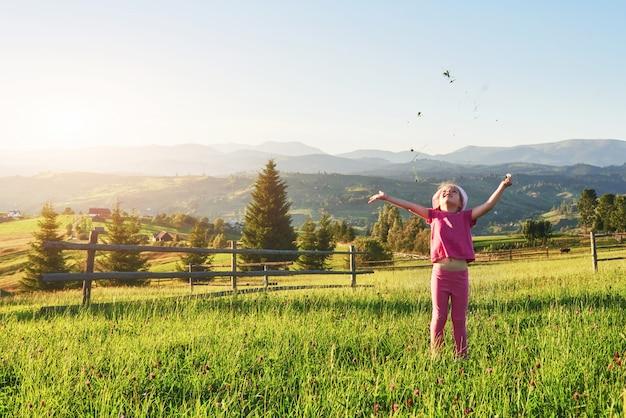 La pequeña niña feliz linda juega al aire libre en el césped y admira las vistas a las montañas. copie espacio para su texto