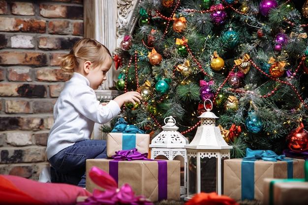 Pequeña niña feliz que adorna el árbol de navidad con los juguetes en días festivos