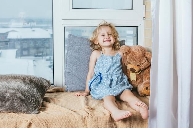 Pequeña niña hermosa y feliz sentada en su casa en un acogedor alféizar con un vestido