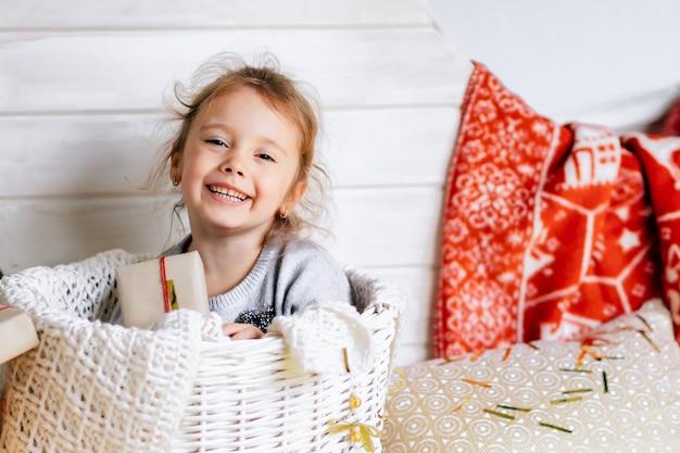 Pequeña niña hermosa se sienta en una canasta en medio de la luna adornada para el año nuevo