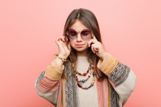 La pequeña niña hippie se concentró en una tarea, manteniéndole los dedos índice apuntando la cabeza.