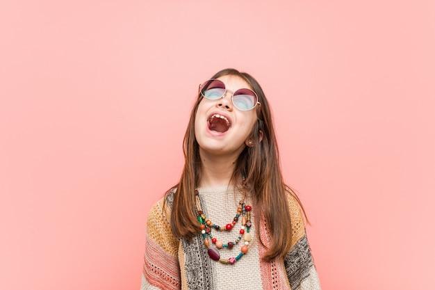 Pequeña niña hippie relajada y feliz riendo, con el cuello estirado mostrando los dientes.