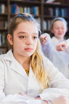 Pequeña niña intimidada llorando en la biblioteca