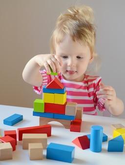 La pequeña niña juega con cubos de madera coloridos