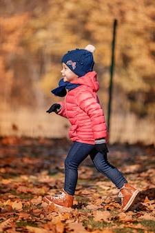 Pequeña niña jugando en hojas de otoño