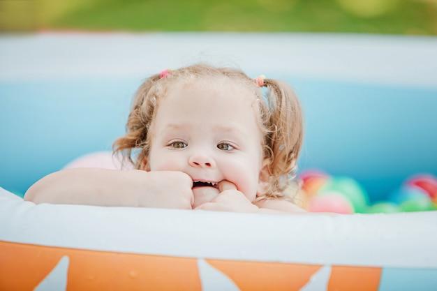 La pequeña niña jugando con juguetes en la piscina inflable en el día soleado de verano