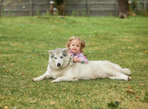 La pequeña niña jugando con perro contra la hierba verde en el parque