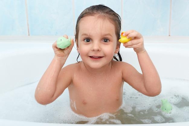 Pequeña niña con juguete en manos tomando baño, juega en el agua con pato y delfín