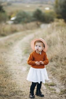Pequeña niña linda afuera en el parque, tiempo de otoño