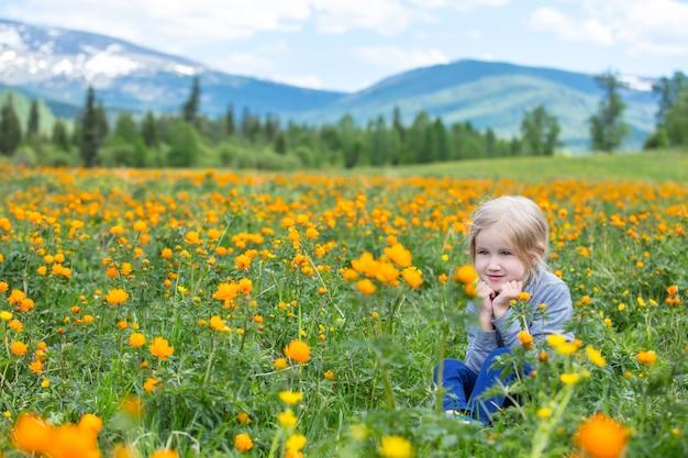 La pequeña niña linda es hermosa y feliz, sonriendo en verano en el prado contra las montañas con nieve