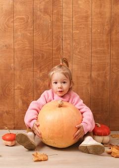 Una pequeña niña linda con un suéter rosa abraza una gran calabaza sentada en el suelo de una madera.