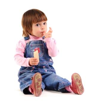 La pequeña niña en mono de jeans sosteniendo la oblea en las manos sobre fondo blanco.