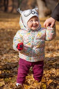 La pequeña niña de pie en hojas de otoño