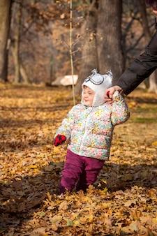 La pequeña niña de pie en las hojas de otoño
