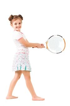 Pequeña niña positiva en ropa elegante de pie y sosteniendo la raqueta de tenis en la mano y sonriendo sobre fondo blanco.