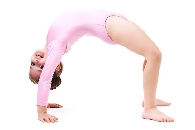 Pequeña niña positiva en traje de gimnasia rosa de pie en pose de puente y sonriendo sobre fondo blanco.
