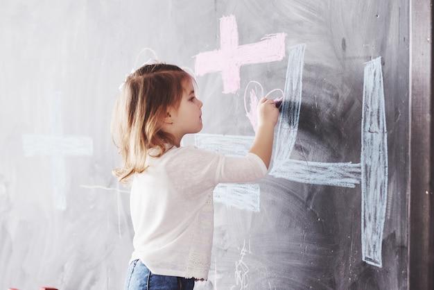 Pequeña niña rizada que dibuja con color del creyón en la pared. obras de niño. linda estudiante escribiendo en la pizarra